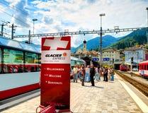 库尔,瑞士, 2010年8月, 20日:在冰川明确全景山火车广告横幅的看法在瑞士路轨小站 免版税库存图片