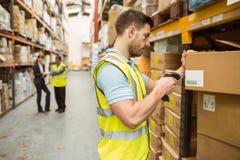 仓库工作者在箱子的扫描条形码 免版税库存照片