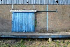 仓库的腐朽的工业门 库存图片