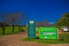 库里奇巴,巴西- 2016年5月12日:在植物园的入口的可喜的迹象在一副情报横幅旁边的 免版税库存图片