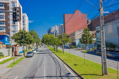 库里奇巴,巴西- 2016年5月12日:有有些汽车的长的空的街道停放了在边和有些树在边路 库存照片