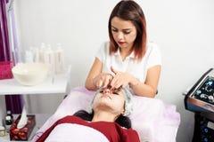 应用一个面部面具的美丽的女性美容师于美容院的一个女性客户 图库摄影