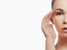 应用一些奶油的美丽的妇女画象于她的护肤的面孔 免版税库存照片