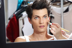 应用与刷子的化妆师基础,化装室镜子的人 免版税库存图片