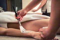 应用使充满活力的湿气香脂的亚裔治疗师在秀丽铈 免版税库存图片