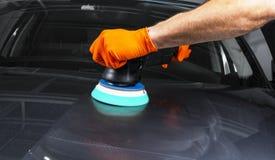 应用保护带的汽车波兰蜡工作者手在擦亮前 抛光的和擦亮的汽车 ( 人举行a polis 免版税库存照片
