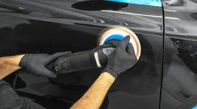 应用保护带的汽车波兰蜡工作者手在擦亮前 抛光的和擦亮的汽车 汽车详述 人举行a polis 库存图片