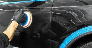 应用保护带的汽车波兰蜡工作者手在擦亮前 抛光的和擦亮的汽车 汽车详述 人举行a polis 免版税库存图片