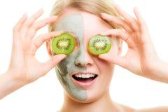 应用关心皮肤透明油漆 黏土面具的妇女与在面孔的猕猴桃 免版税库存图片