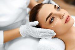 应用关心皮肤透明油漆 在妇女的面孔的化妆奶油 秀丽温泉处理 库存图片