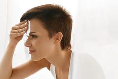 应用关心皮肤透明油漆 妇女与油引人入胜的纸的清洁面孔 免版税库存图片