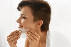 应用关心皮肤透明油漆 妇女与油引人入胜的纸的清洁面孔 免版税图库摄影