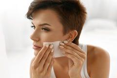 应用关心皮肤透明油漆 妇女与油引人入胜的纸的清洁面孔 库存照片