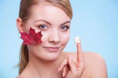 应用关心皮肤透明油漆 少妇女孩的面孔有红槭的 图库摄影