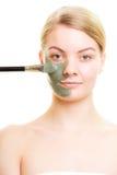 应用关心皮肤透明油漆 应用黏土在面孔的妇女泥面具 图库摄影