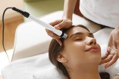 应用关心皮肤透明油漆 得到面部氧气喷气机削皮治疗的妇女 免版税库存图片