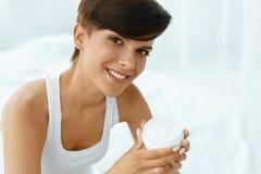 应用关心皮肤透明油漆 拿着面霜,化妆水的美丽的愉快的妇女 库存照片