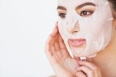 应用关心皮肤透明油漆 有板料面具的美丽的女孩在她的面孔 库存图片