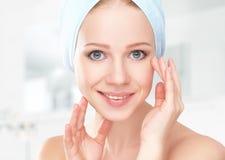 应用关心皮肤透明油漆 毛巾的年轻美丽的健康女孩在卫生间里 免版税库存图片