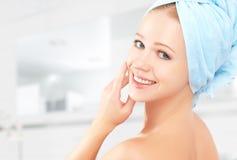 应用关心皮肤透明油漆 毛巾的年轻美丽的健康女孩在卫生间里 免版税库存照片