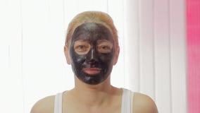 应用关心皮肤透明油漆 适用与刷子黏土泥面具的妇女于她的面孔演播室射击 股票视频