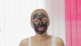 应用关心皮肤透明油漆 适用与刷子黏土泥面具的妇女于她的面孔演播室射击 影视素材