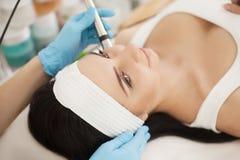 应用关心皮肤透明油漆 得到她的皮肤Analized的美丽的健康妇女由美容师,使用皮肤分析仪专业秀丽设备 免版税图库摄影