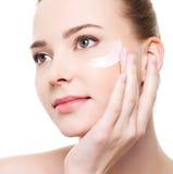 应用化妆用品在妇女附近注视 库存照片