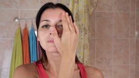 应用反皱痕奶油的少妇 美丽的女孩在面孔上把奶油放在卫生间 有吸引力的妇女年轻人 股票视频