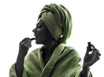 应用唇膏剪影的妇女 免版税库存图片