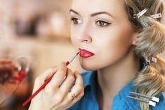 应用唇膏的化妆师 免版税库存照片