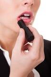 应用唇膏的可爱的女实业家 免版税库存图片