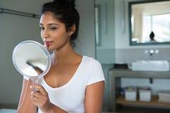 应用唇膏的妇女在卫生间里 免版税库存照片