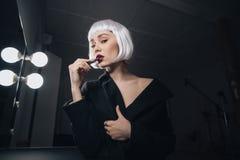 应用唇膏的白肤金发的假发的肉欲的妇女在化装室 免版税库存照片
