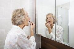 应用唇膏的资深妇女,当看镜子在卫生间里时 免版税库存照片