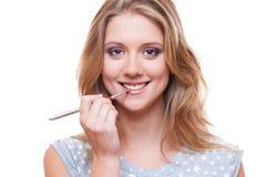 应用唇膏的兴高采烈的妇女 免版税库存图片