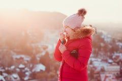 应用嘴唇凤仙花的妇女,当步行在一冷漠的天时 免版税库存图片