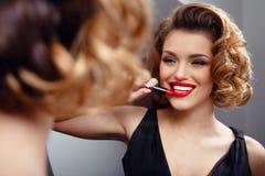 应用在嘴唇的诱人的性感的年轻女人红色口红,看在镜子 减速火箭的概念 使用化妆用品 免版税库存图片