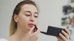 应用在她的嘴唇的妇女唇膏在镜子前面 股票视频