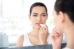 应用在她的嘴唇的少妇香脂临近镜子 免版税库存图片