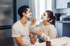 应用在她的男朋友的面孔的妇女黏土面具 年轻爱恋的夫妇在家照料皮肤 免版税库存图片