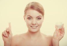 应用在她的皮肤面孔的妇女奶油 图库摄影