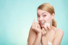 应用在她的皮肤面孔的妇女奶油 库存图片