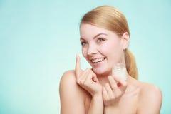 应用在她的皮肤面孔的妇女奶油 免版税库存照片