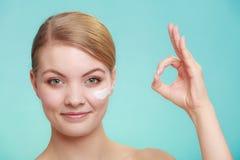 应用在她的皮肤面孔的妇女奶油 免版税图库摄影