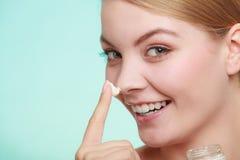应用在她的皮肤面孔的妇女奶油 库存照片