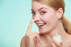 应用在她的皮肤面孔的妇女奶油 免版税库存图片