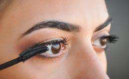 应用在她的眼睛的妇女染睫毛油 免版税库存图片