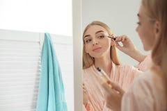 应用在她的睫毛上的少妇油临近镜子户内 库存图片