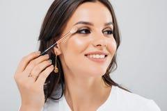 应用在她的睫毛的美丽的妇女染睫毛油-在白色背景 库存照片